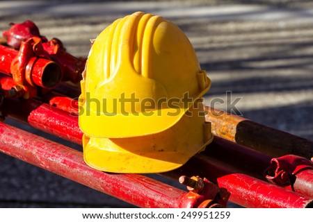 yellow hardhat on construction site - stock photo