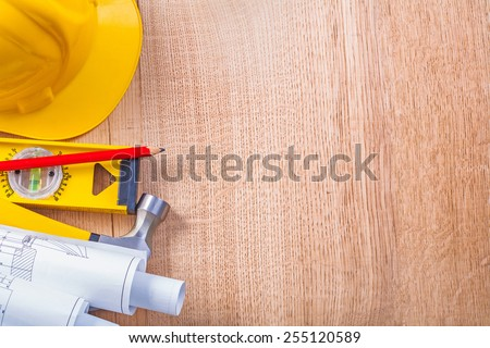 yellow hardhat rolled white blueprints level red pencil and claw hammer on wooden board copyspace construction concept background   - stock photo