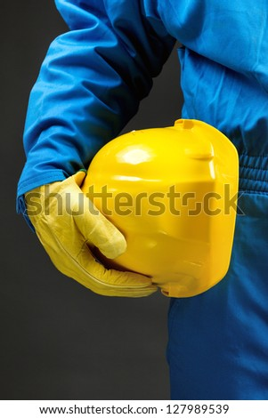 Yellow hardhat under arm. Part of body - stock photo