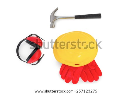 Yellow hardhat with protective gloves, earmuffs and hammer on white background - stock photo