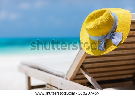 Yellow hat on a lounge chair at tropical beach - stock photo