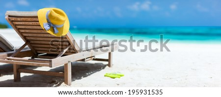 Yellow hat on a lounge chair at tropical beach panorama - stock photo