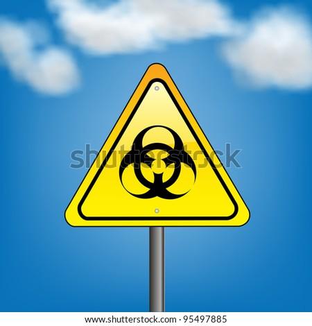 Yellow hazard warning sign on against blue sky - biohazard symbol sign warning - stock photo
