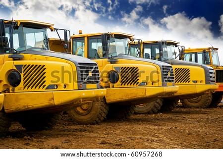 Yellow heavy construction tipper trucks - stock photo