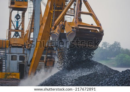 Yellow heavy excavator and bulldozer unloading road metal during road construction work  - stock photo