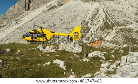 Yellow helicopter used for rescue operations, On the ground in Dolomites, Italy. Helicopter rescue