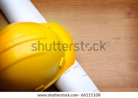 yellow helmet and paper roll - stock photo