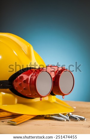yellow helmet and wood mounting tools on wooden table