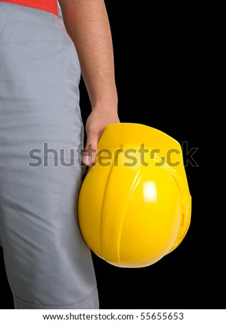 Yellow helmet at man hands isolated on a black