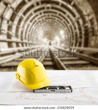 yellow helmet for workers security bubble level and blueprint paper plan lie on table against background of an underground mine with arc legs and rails for trolleys with coal in perspective - stock photo