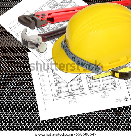 Yellow Helmet of labor constructor with blueprints building construction and tools, metal tape measure, hammer, wrench