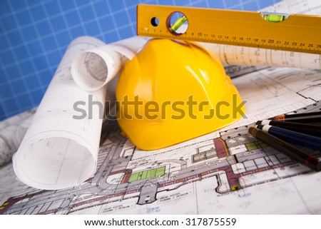 Yellow helmet, project drawings and house model - stock photo