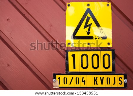 Yellow high voltage caution sign on red wooden wall - stock photo