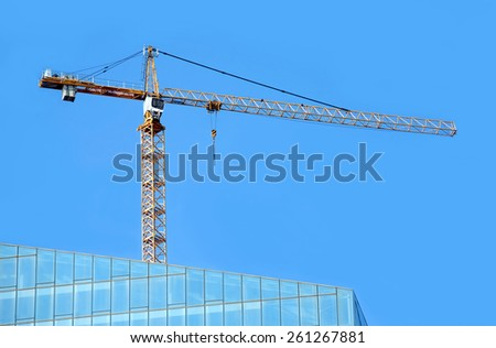 Yellow hoisting tower crane on top of construction skyscraper building over cloudless blue sky - stock photo