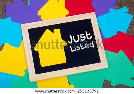 Yellow home sign on the blackboard: Real Estate Concept, Just listed - stock photo