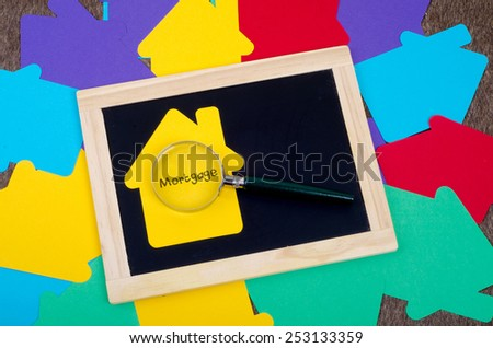 Yellow home sign with magnifying glass and blackboard: Real Estate Concept, Mortgage - stock photo