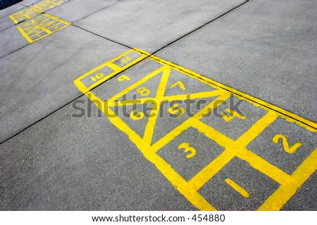 yellow hopscotch boards painted on cement at a schoolyard - stock photo