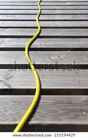 Yellow hose lines terrace boards - stock photo