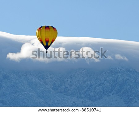 Yellow hot air balloon against a snowy mountain peak - stock photo