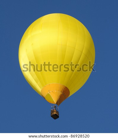Yellow hot air balloon floating overhead - stock photo