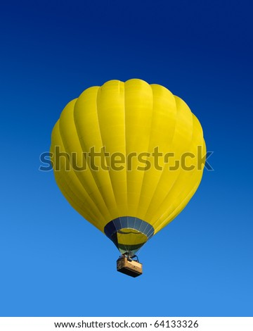 Yellow hot air balloon flying on dark blue sky background - stock photo