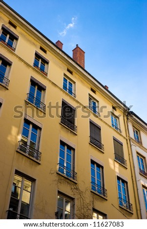 Yellow house facade with blue sky reflection in windows
