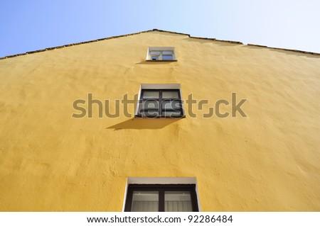 Yellow House Facade with Windows - stock photo