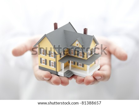 Yellow house in hands - stock photo