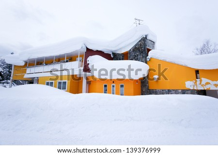 Yellow house in snow - stock photo