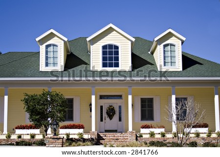 Yellow house on a very bright day in Florida - blue, blue sky above. - stock photo