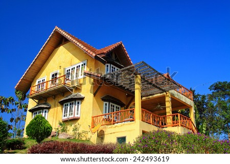yellow house with blue sky - stock photo
