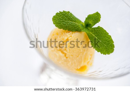 yellow ice cream with mint in a glass