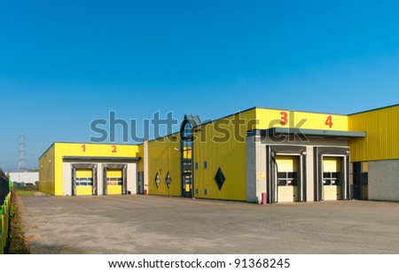 yellow industrial warehouse with numbered loading docks - stock photo
