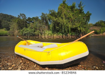 Yellow inflatable boat on river shore