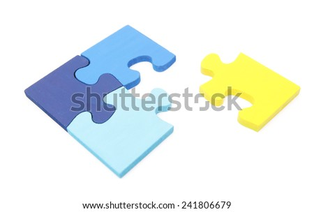Yellow jigsaw puzzle piece going into a blue jigsaw puzzle - stock photo