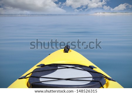 Yellow kayak on the ocean heading towards the beach with blue sky and clouds - stock photo