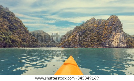 Yellow kayak on turquoise sea water amongst the rocks of Halong Bay. Creative effect panorama