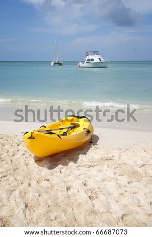 Yellow kayak pulled onto the beach in the Caribbean. A motorboat and a sailboat are anchored in the distance. - stock photo