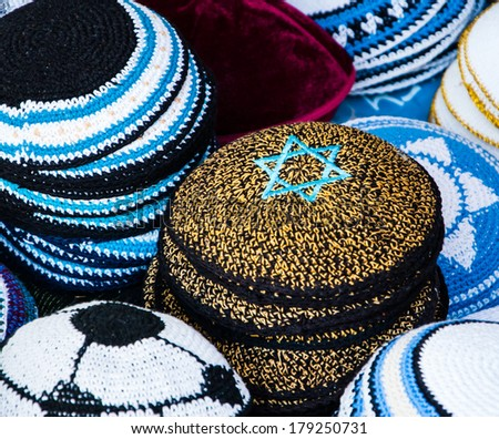 Yellow Kippah with blue Magen David (Star of David) and other Yarmulkes for sale at the market in Jerusalem (Israel). Closeup. Selective focus on the upper corner of the Magen David. Jewish background - stock photo