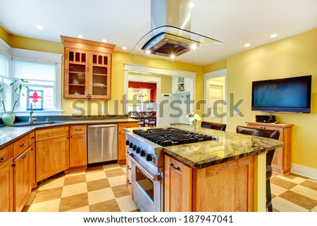 Yellow kitchen interior. View of island with built-in stove and kitchen hood above it - stock photo