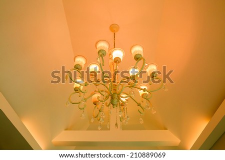 Yellow lamps and crystal chain on ceiling in ballroom  - stock photo