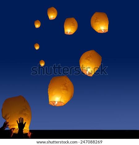 yellow lantern in human hands on dark background - stock photo