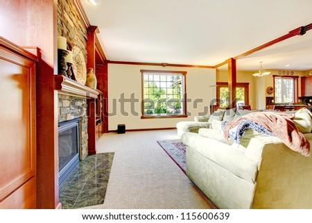 Yellow large luxury living room with fireplace and sectional sofa with beige carpet. - stock photo