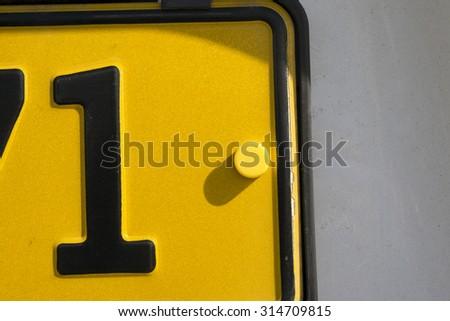 Yellow lawful Danish license plate closeup. - stock photo