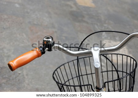 Yellow leather grip, black bicycle bell and front basket - stock photo