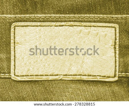 yellow leather label on yellow-brown jeans background  - stock photo