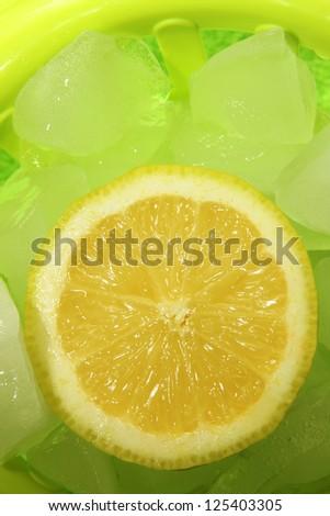 yellow lemon and green ice cubes - stock photo
