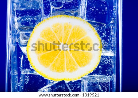 Yellow lemon in the glass of cold sparkling water and ice. - stock photo