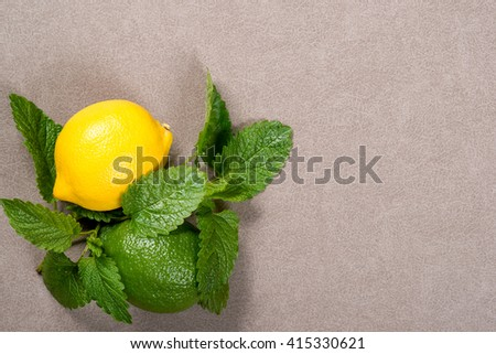 Yellow lemon, lime and green mint leaves on the table. Top view  - stock photo