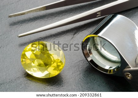 Yellow lemon quartz gemstone with tweezers and loupe on black stone plate. - stock photo